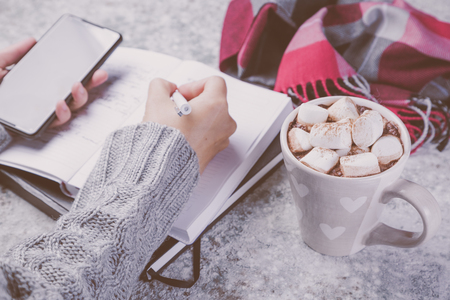 Winter cozy workspace with computer, phone, notepad, cocoa Stock Photo