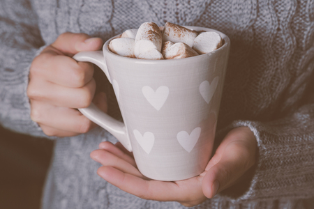 Hands holding cup of hot chocolate in grey sweater