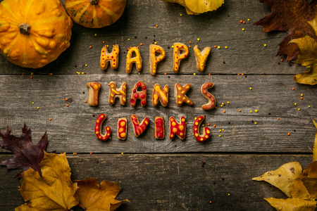Thanksgiving concept - text with cookies, leaves, pumpkins