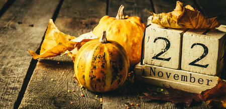 Thanksgiving concept - wood calendar with yellow leaves and pumpkins, wood background, toned Stock Photo