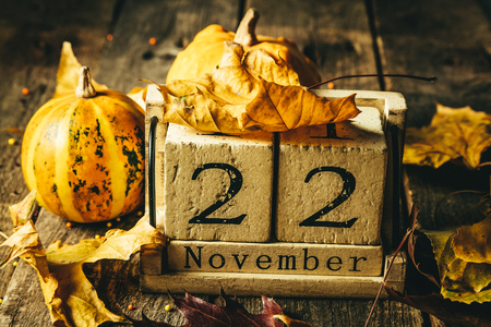 Thanksgiving concept - wood calendar with yellow leaves and pumpkins