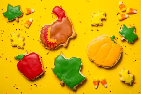 Thanksgiving concept - cookies shaped like pumpkin, turkey, leaves on bright yellow background, top view