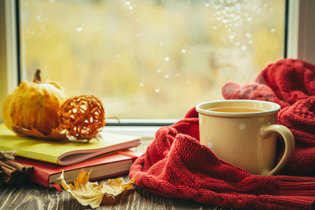 Autumn tea with scarf and leaves in front of window