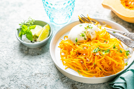 Butternut squash noodles with mozzarela, pecans, herbs 写真素材 - 111361235