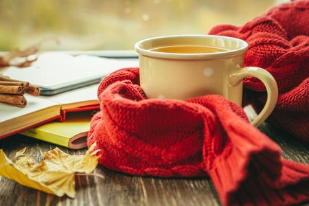Jesienna herbata z szalikiem i liśćmi przed oknem Zdjęcie Seryjne