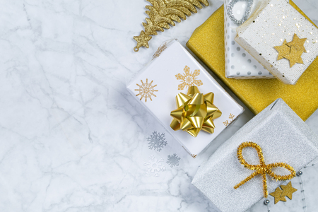 Christmas concept - silver and gold presents with confetti anf ribbon Stock Photo - 111361301