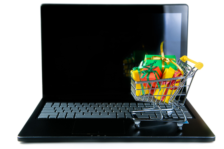 Ciber monday concept - trolley cart with christmas presents on notebook Foto de archivo - 111344886