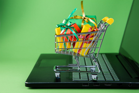 Ciber monday concept - trolley cart with christmas presents on notebook