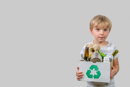 Niño tiene caja con materiales reciclables.
