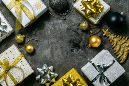 Christmas concept - silver and gold presents with confetti and ribbon