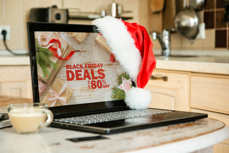 Online shopping concept - computer with sales banner, Santa hat, coffee