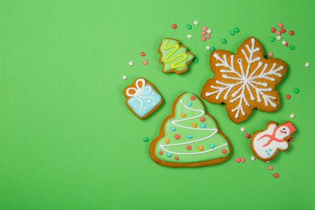 Christmas concept - gignerbread cookies on bright green background