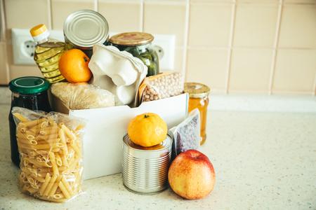 Food donations in box in kitchen Foto de archivo
