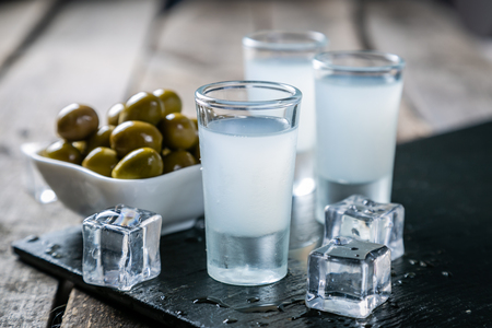 Traditional greek vodka - ouzo in shot glasses Stock Photo - 113299434