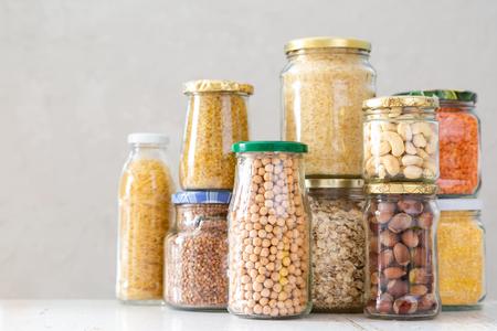 Diverse ongekookte granen, granen, bonen en pasta voor gezond koken in glazen potten