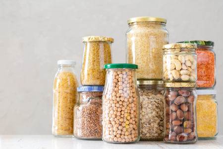 Various uncooked cereals, grains, beans and pasta for healthy cooking in glass jars