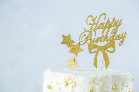 Golden birthday concept - cake, presents, decorations Standard-Bild