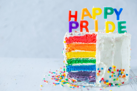 Happy pride day - rainbow layered cake with candles. Tolerance and equality for lgbt community, same sex marriage