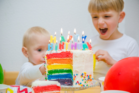 Birthday party concept - colourful cake with candles and kids Фото со стока