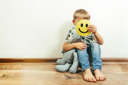 Depressieve jongen die een glimlach vasthoudt en doet alsof hij in orde is. Gezicht van de depressie