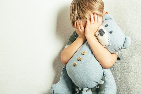 Sad depressed boy with teddy bear Standard-Bild - 114105599