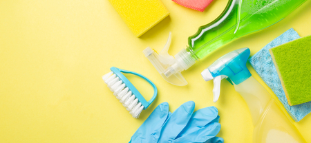 Cleaning concept - cleaning supplies on pastel yellow background