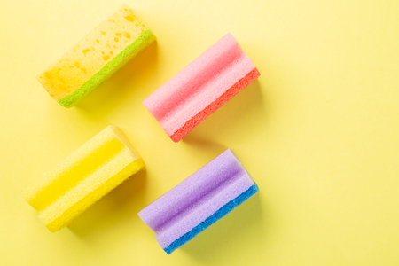 Cleaning concept - pastel colour sponges on yellow background