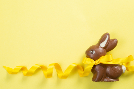 Easter background - chocolate bunny with yellow ribbon