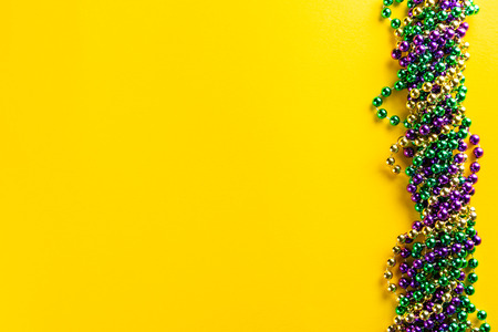 Mardi gras carnival concept - beads on yellow background