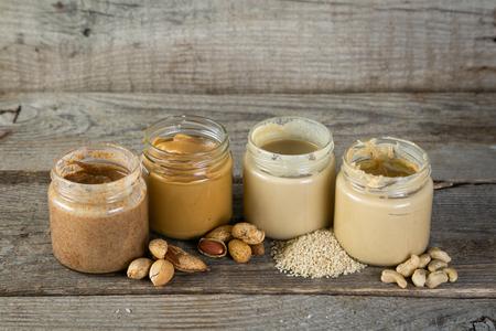 Selectie van notenpasta - pinda-, cashew-, amandel- en sesamzaad Stockfoto