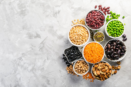 Selection of legumes in white bowls on stone background