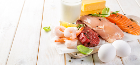 Selection of aminal protein sources on wood background 스톡 콘텐츠