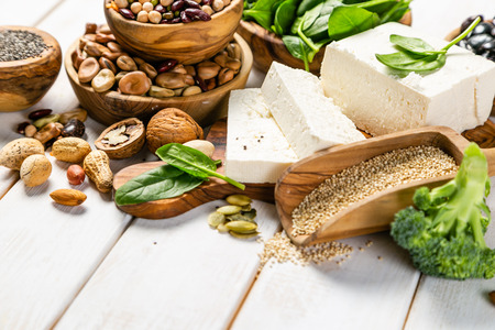 Selection of vegan plant protein sources - tofu, quinoa, spinach, broccoli, chia, nuts and seeds