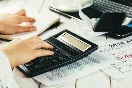 Tax day concept - calculator, calendar, tax form, hands Stock Photo