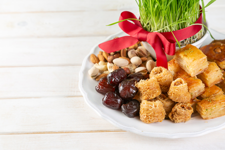Nowruz holiday concept - grass, baklava sweets, nuts and seeds Stock Photo