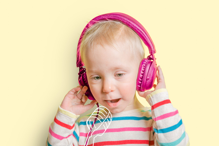 Young toddler girl listening to headphones and singing to imaginery mic Reklamní fotografie