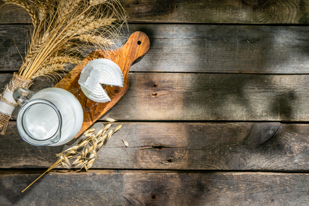 Shavout concept - grains, milk and cheese on wood background