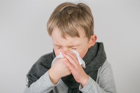 Sick boy sneezes, grey background Stock Photo