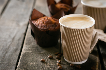 Coffee to go with muffin on wood background, copy space