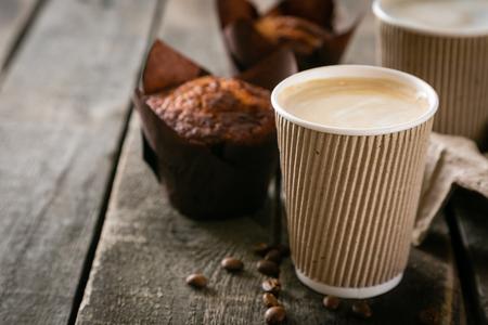 Kaffee zum Mitnehmen mit Muffin auf Holzhintergrund, Kopierraum