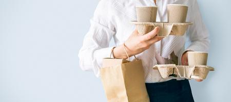 Vrouw met koffiecontainers, papieren zak met voedselcontainers. Eten en koffie bezorgen. Stagiair op eerste baan