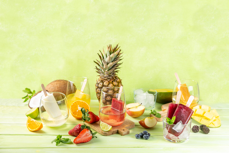 Selection of colourful ice pops and ingredients on green wood background