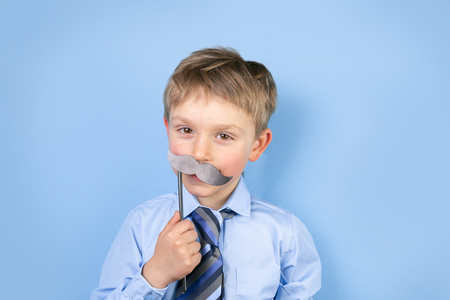Fathers day concept - boy wears formal shirt and tie just blue background