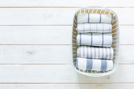 Concept de rangement Marie Kondo - linge de cuisine plié dans un panier blanc