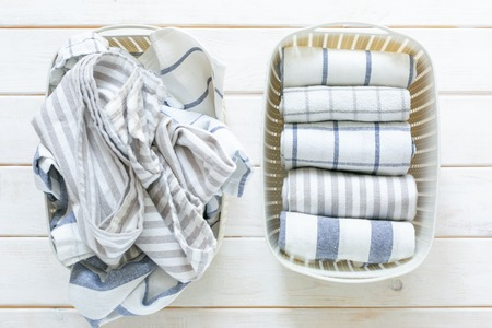 Marie Kondo tidying concept - folded kitchen linens in white basket