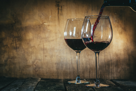 Red wine in glasses on rustic background