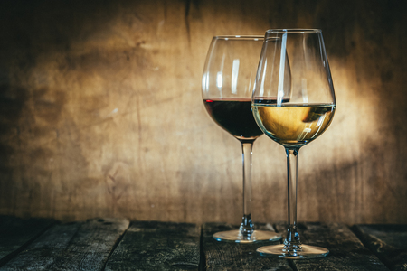 Red and white wine in glasses on rustic background 스톡 콘텐츠