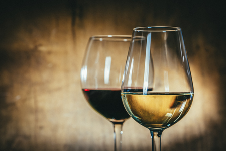 Red and white wine in glasses on rustic background Фото со стока