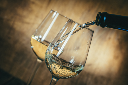 White wine in glasses on rustic background