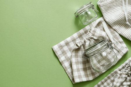 Zero waste concept - reusable cotton bags and glass jars on green Stock Photo